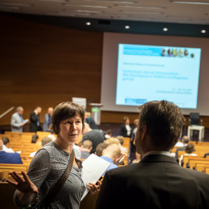 Blick von hinten in den Hörsaal des Umweltbundesamtes. Auf den Plätzen sitzen Veranstaltungsteilnehmerinnen und -teilnehmer und schauen auf eine Präsentation nach vorne. Zwei Personen diskutieren im Vordergrund.