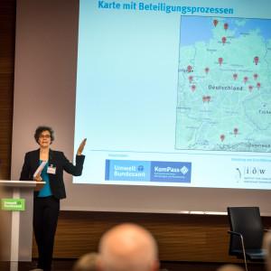 Vortragende steht am Rednerpult und zeigt auf Deutschlandkarte im Hintergrund. Die Karte zeigt an in Rot markiert, wo Beteiligungen bereits stattfinden.