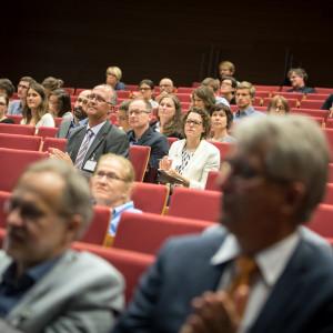 Blick von vorne in die Sitzreihen des Hörsaales. Veranstaltungsteilnehmerinnen und -nehmer sitzen zuhörend auf roten Reihenstühlen.