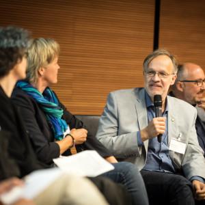 Personen sitzen zur Interviewrunde. Ein Teilnehmer hält das Mikrofon in der Hand und spricht hinein.
