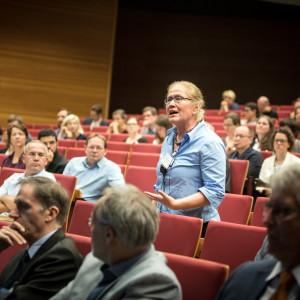 Teilnehmerin steht präsent im Hörsaal innerhalb der roten Stuhlreihen und spricht. Die anderen Teilnehmerinnen und Teilnehmer sitzen rundherum und hören zu.