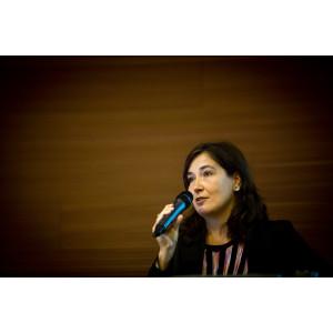 Moderatorin spricht auf dem Podium ins Handmikro