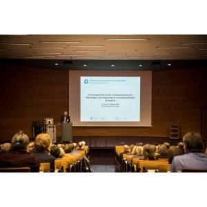 Ein Vortragender steht vor dem Hintergrund der Präsentation am Rednerpult