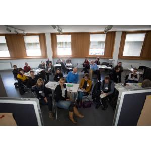 Teilnehmer sitzen an Arbeitsgruppentischen