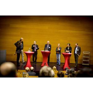 Moderatoren stehen an den Stehtischen auf dem Podium