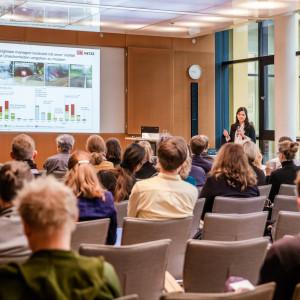 Teilnehmende folgen auf beigen Stühlen in Reihen sitzend einer Präsentation. Die Vortragende steht mit Handmikrofon nahe Stehpult vor einer Fensterfront.