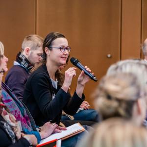 Eine Teilnehmerin spricht angeregt ins Handmikrofon. Alle Teilnehmende sitzen in Reihen im Veranstaltungsraum. Die Wände sind holzvertäfelt.