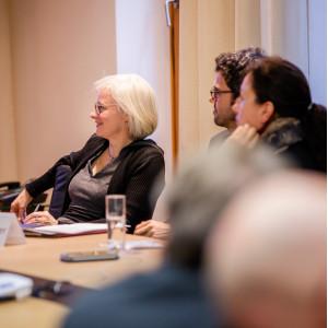 Teilnehmende sitzen im Workshopraum zusammen und schauen zuhörend in eine Richtung in einem hellen Raum.