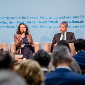 Podiumsdiskussion vor hellblauem Hintergrund, auf dem der Veranstaltungsort geschrieben steht.