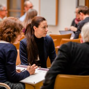 Teilnehmende haben sich in Gruppen im Veranstaltungsraum zusammengesetzt auf orangenen Stühlen und sprechen miteinander. Ergebnisse werden dabei auf Arbeitsbögen von einer Teilnehmerin skizziert.