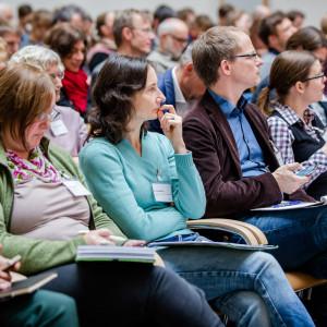 Teilnehmende sitzen auf Stühlen in Reihen und beschäftigen sich mit Schriftgut in ihren Händen.