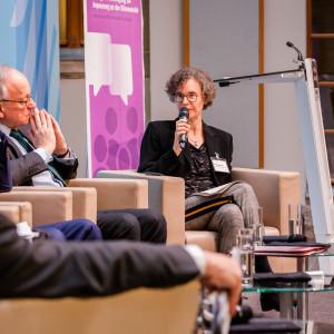 Podiumsdiskussion aus einer anderen Perspektive. Im Hintergrund steht ein Rollup in lila Farbtönen mit Veranstaltungstitel. Die Moderatorin spricht in das Mikrofon.