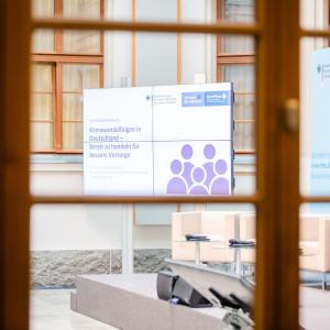 Blick durch das hölzerne Fensterkreuz eines Workshopraumes in den Innhof auf den Titelaufsteller sowie die Podiumsausstattung, wie Sessel, Tische, Mikrofone.