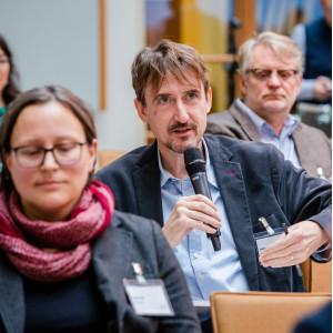 Ein Teilnehmer sitzt im Veranstaltungsraum mit den anderne Teilnehmenden und spricht ins Handmikrofon.
