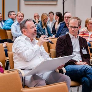 Teilnehmende sitzen im einem Veranstaltungsraum auf orangenen Stühlen in Reihen und blicken nachdenklich. Ein Teilnehmer spricht in ein Handmikro und hält ein Tableau in der Hand.