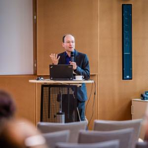 Ein Vortragender steht vor dem geöffnetem Laptop gestikulierend am Stehpult im holzfarben vertäfelten Veranstaltungsraum. Der Vortragende trägt einen dunkelfarbenen Anzug.