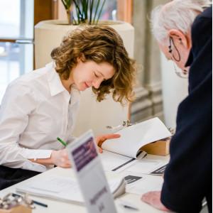Ein Teilnehmender registriert sich am Registriertisch und trägt sich in die Teilnehmendenliste ein. Eine Dame in einer weißen Bluse trägt Angaben in eine Liste ein.