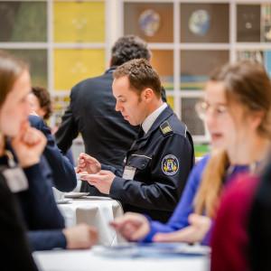 Teilnehmende stehen in der Kaffeepause an Stehtischen zusammen und tauschen sich rege aus. Ein uniformierter Teilnehmender isst Kuchen.