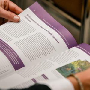 Der Blick geht in den Monitoringbericht, den ein Teilnehmender mit beiden Händen aufgeschlagen hält. Die Seiten sind lila abgesetzt und bebildert.