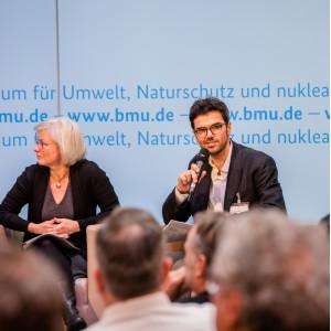 Podiumsdiskussion vor dem hellblauem Hintergrund, auf dem der Veranstaltungsort geschrieben steht. Ein Teilnehmender hält ein Handmikrofon.