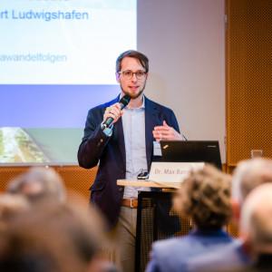 Vortragender steht mit Mikrofon in der Hand am Stehpult. Im Hintergrund ist seine Präsentation abgebildet.
