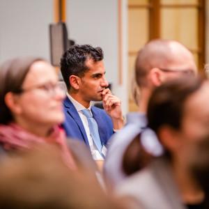 Der Blick geht durch die Teilnehmenden auf einen Teilnehmer, der sehr nachdenklich schaut. Er trägt einen blauen Anzug mit hellblauem Schlips und weisses Hemd. Der Raum ist hell und holzfarben abgesetzt.