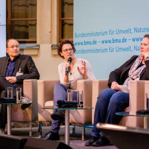 Podiumsdiskussion vor dem hellblauem Hintergrund, auf dem der Veranstaltungsort geschrieben steht. Eine Teilnehmende hält ein Handmikrofon und spricht angeregt zu den anderen Podiumstteilnehmenden.