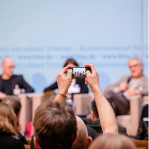 Ein Teilnehmer hält ein Smartphone in die Luft in Richtung Podium und macht ein Foto.