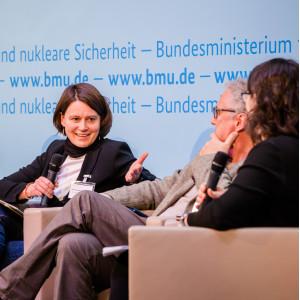 Podiumsdiskussion vor dem hellblauem Hintergrund, auf dem der Veranstaltungsort geschrieben steht. Eine Teilnehmende hält ein Handmikrofon und spricht angeregt zu den anderen Podiumsteilnehmenden.