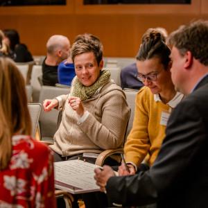 Teilnehmende haben sich im Saal zu Arbeitsgruppen zusammengefunden und sprechen zusammen. Die Stühle sind mit beigen Stoff bezogen und die Raumwände sind holzvertäfelt.