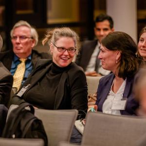 Teilnehmende sitzen im Veranstaltungsraum in Reihen und unterhalten sich lachend.
