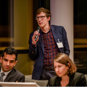 Teilnehmender steht im Veranstaltungsraum und spricht in ein Mikrofon, welches er in seiner rechten Hand hält.