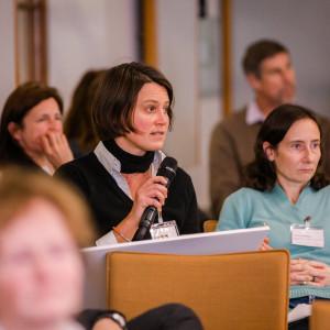 Teilnehmende sitzen im einem Veranstaltungsraum auf orangenen Stühlen in Reihen und blicken nachdenklich. Eine Teilnehmerin spricht in ein Handmikro.