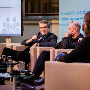Podiumsdiskussion vor dem hellblauem Hintergrund, auf dem der Veranstaltungsort geschrieben steht. Ein Teilnehmender hält ein Handmikrofon in seiner Hand.