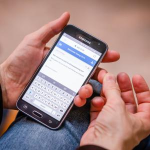 Ein Teilnehmer zeigt auf seinem Smartphone die digitale Befragung: Was müssen wir jetzt für den Klimawandel tun ?