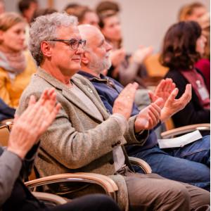 Teilnehmende sitzen auf orangenen Stühlen in Reihen im Veranstaltungsraum und applaudieren.