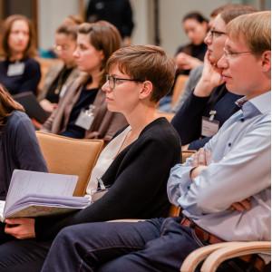 Teilnehmende sitzen im Veranstaltungsraum auf orangenen Stühle in Reihen und schauen zuhörend in eine Richtung.