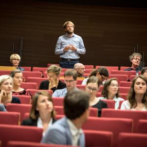 Teilnehmer steht präsent im Hörsaal innerhalb der roten Stuhlreihen und spricht. Die anderen Teilnehmerinnen und Teilnehmer sitzen rundherum und hören zu.