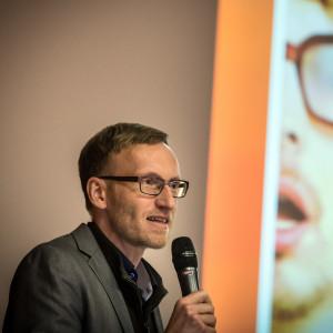 Vortragender steht mit Mikrofon in der Hand neben seiner Präsentation.