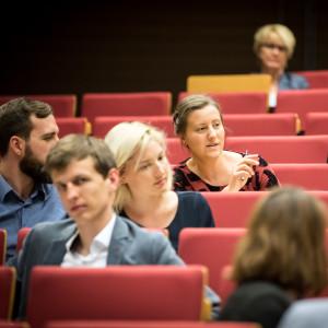 Blick auf miteinander diskutierende Veranstaltungsteilnehmerinnen und -teilnehmer  im Hörsaal.