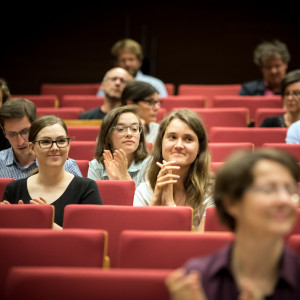 Teilnehmerinnen und Teilnehmer sitzen applaudierend in den roten Stuhlreihen des Hörsaales.