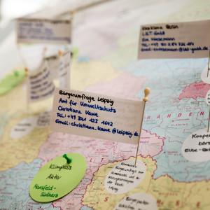 Auf kleinen Fahnen und kleine runde Moderationskreisen stehen Informationen zu Beteiligung. Diese markieren den Ort auf einer Deutschlandkarte.