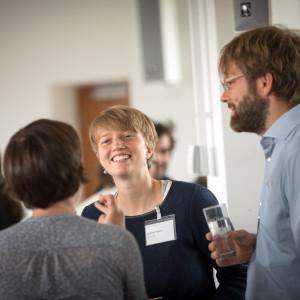 Teilnehmerinnen und Teilnehmer stehen unterhaltend und lachend beisammen.