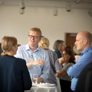 Teilnehmerinnen und Teilnehmer stehen während der Pause unterhaltend beisammen. Ein Teilnehmer hält ein Wasserglas in der Hand und spricht.