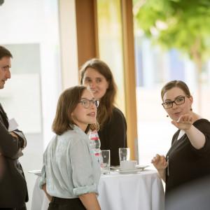 Teilnehmer und Teilnehmerinnen stehen in der Pause am Bistrotisch. Sie folgen schauend dem Hinweis einer Teilnehmerin, die in eine Richtung zeigt. Auf dem Bistrotisch stehen Gläser, Tassen und Teller sowie ein Getränkeflasche.Auf dem B