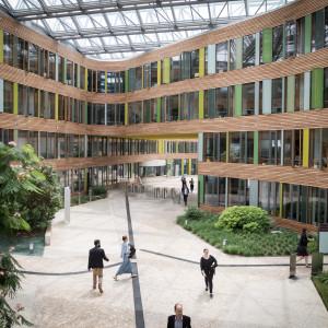 Blick von einer Brücke im Atrium des Umweltbundesamtes auf Teilnehmerinnen und Teilnehmer auf dem Weg zu den Workshopräumen. Das Atrium ist begrünt, die Innenfassade besteht aus Holz und Glas.