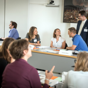 Teilnehmerinnen und Teilnehmer sitzen unterhaltend im Workshopraum am Tisch. Ein Teilnehmer steht dabei vor einem in dunklen Farben gehaltenes Wandbild.
