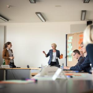 Vortragende steht an mit Moderationskarten bestückte Moderationswand und hält beschriftete orangene Moderationskarte in der Hand und spricht in den Raum, wo andere Teilnehmerinnen und Teilnehmer am Tisch in Reihe sitzend zuhören. Im Hintergrund steht eine weitere Teilnehmerin.
