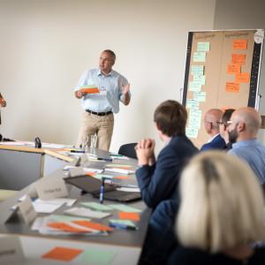 Vortragender steht an mit Moderationskarten bestückte Moderationswand und hält beschriftete orangene und grüne Moderationskarte in der Hand und spricht in den Raum, wo andere Teilnehmerinnen und Teilnehmer am Tisch in Reihe sitzend zuhören. Im Hintergrund steht eine weitere Teilnehmerin.