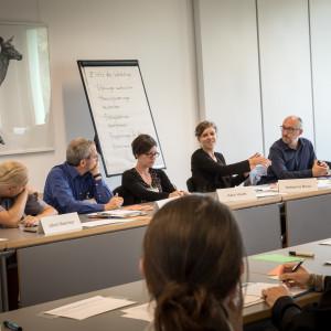 Teilnehmerinnen und Teilnehmer sitzen sich gegenüber in Reihe und diskutieren miteinander. Im Hintergrund steht ein Flipchart. An der Wand hängt ein Bild mit einem Reh darauf.